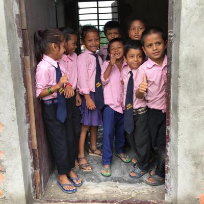 Students stand in the doorway of their classroom in Nepal.